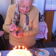 Maisie cutting her 90th birthday cake