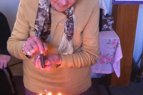 Maisie cutting her 90th birthday cake